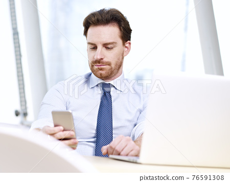 caucasian businessman sitting at desk looking at mobile phone in office 76591308