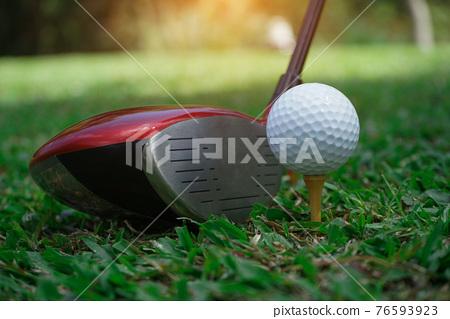 Golf club and golf ball close up in grass field with sunset. Golf ball close up in golf coures at Thailand. 76593923