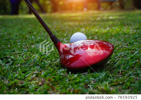 Golf club and golf ball close up in grass field with sunset. Golf ball close up in golf coures at Thailand. 76593925
