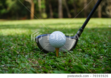 Golf club and golf ball close up in grass field with sunset. Golf ball close up in golf coures at Thailand. 76593926
