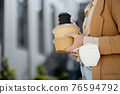 Woman have outdoor lunch on stairs near office building 76594792