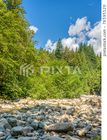 Dried stoney waterway of montailn river on bright summer day 76595520