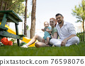 Happy parents and their cute son sit on the grass - looking into the camera 76598076