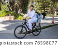Father with his son on the back riding a bicycle 76598077
