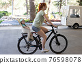 Mother with her son on the back riding a bicycle 76598078