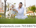 Happy father and his cute son sit on the grass - looking into the camera 76598079