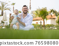 Happy father and his son sit on the grass - looking into the camera 76598080