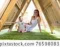 Cute baby and his mother sits under a wooden roof on the playground - looking in the camera 76598083