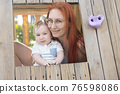 Cute baby and his mother sits in a wooden house on the playground - looking in the camera 76598086
