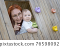 Little baby and his mother sits in a wooden house on the playground - looking in the camera 76598092