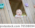 Funny baby sits in a wooden house on the playground 76598094
