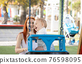 Happy family vacation - funny baby swings on swings in playground and his mom sits near him 76598095