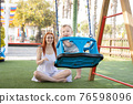 Funny baby swings on swings in playground and his mom sits near him 76598096