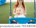 A little laughing baby on swings on an outside playground with his ginger mother 76598098