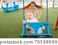 A little laughing boy on swings on an outside playground with his ginger mother 76598099