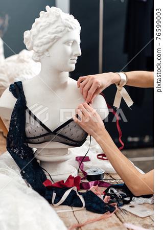 Female lingerie designer working on a bra 76599003
