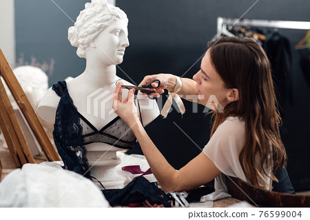 Female lingerie designer working on a bra 76599004