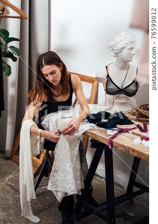 Female lingerie designer works in her workshop. 76599012