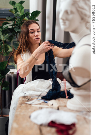 Girl sitting at a table holding tissues 76599013