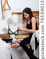 Female fashion designer tries on a brassiere on statue 76599015