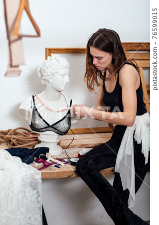 Female fashion designer tries on a brassiere on statue 76599015