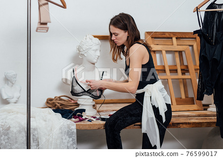 Woman fashion designer tries on a bra on a mannequin 76599017