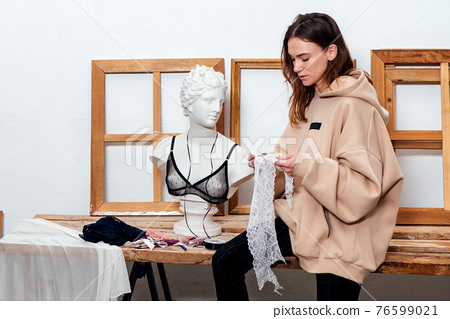 Woman clothing designer sits on the edge of a table and holds a piece of fabric in her hand 76599021
