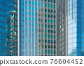 Pattern of office buildings windows. Glass architecture facade design with reflection in urban city, Downtown Dubai. Urban city in financial district with blue sky. 76604452