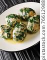 Strangolapreti in Trentino Italian bread and spinach dumplings close-up in a plate. Vertical 76612988