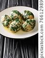 Spinach and Cheese Breadcrumb Dumplings Strangolapreti close-up in a plate. Vertical 76612989