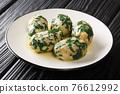 Strangolapreti alla Trentina are tasty gnocchi made with bread, spinach close-up in a plate. Horizontal 76612992