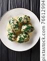 Strangolapreti in Trentino Italian bread and spinach dumplings close-up in a plate. Vertical top view 76612994
