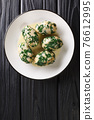 Spinach and Cheese Breadcrumb Dumplings Strangolapreti close-up in a plate. Vertical top view 76612995