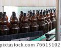 Plastic bottles for beer or carbonated beverage moving on conveyor 76615102