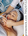 Professional beautician woman massaging face to 76620722