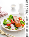 Salmon fish fillet grilled and vegetable salad with radish, tomato, green pepper, broccoli and asparagus. 76621310
