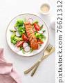 Salmon fish fillet grilled and vegetable salad with radish, tomato, green pepper, broccoli and asparagus. 76621312