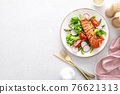 Salmon fish fillet grilled and vegetable salad with radish, tomato, green pepper, broccoli and asparagus. 76621313