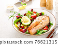 Salmon fish steak grilled, avocado and fresh vegetable salad with tomato, bell pepper and leafy vegetables 76621315