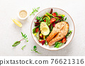 Salmon fish steak grilled, avocado and fresh vegetable salad with tomato, bell pepper and leafy vegetables. Top view 76621316