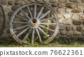 Old cartwheel by the stone wall of an old building 76622361