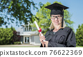 Middle aged woman with diploma in hand. Wearing a graduate uniform 76622369