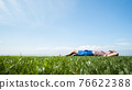 Happy barefoot woman lies on the green grass, rejoices in the heat and summer 76622388