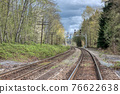 Curve of rail road pathways leading to a city 76622638