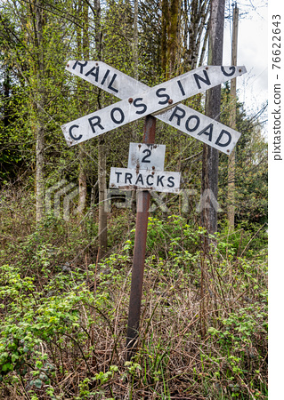 Old sign of railroad crossing on spring trees background 76622643