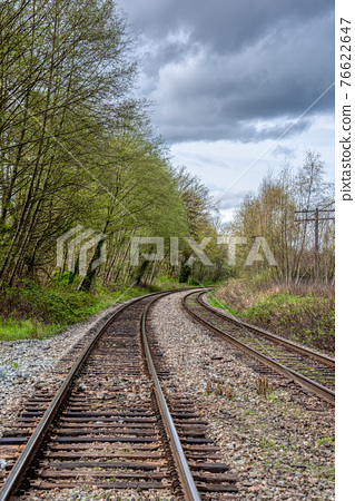 Curve of rail road pathways leading to a city 76622647