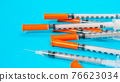 Insulin vial and syringe on blue background 76623034
