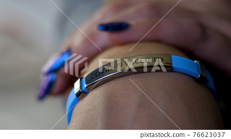 Female hand with vaccined bracelet or label after injection 76623037