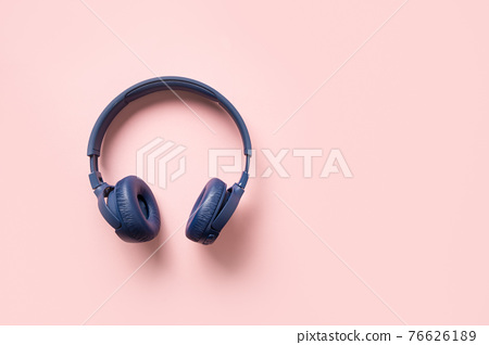 Blue wireless headphones on a pink background. 76626189