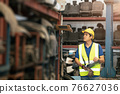 Asian male worker working to checking products stock inventory at warehouse shelf 76627036